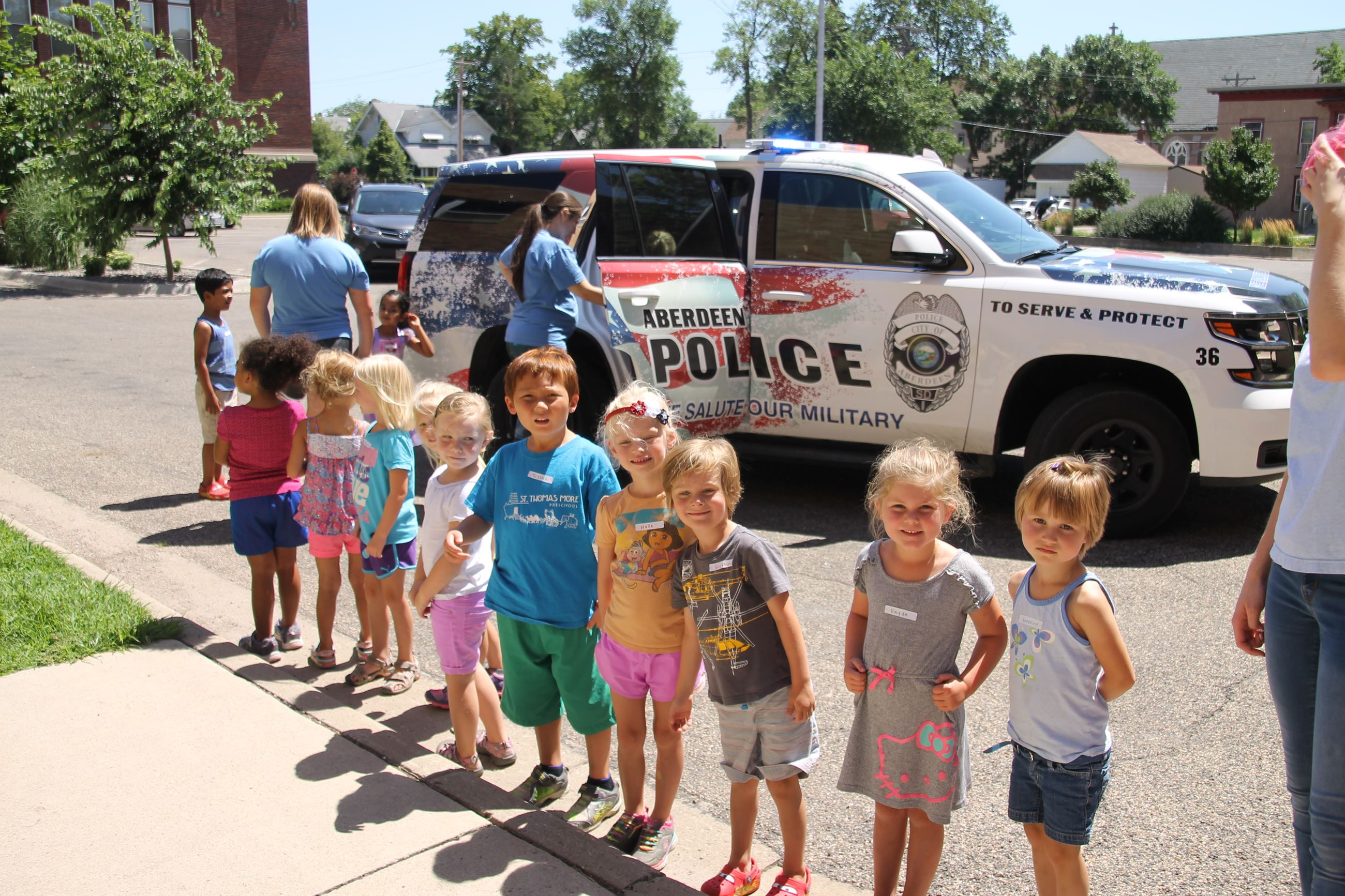 Children looking at a police car during Safety Town
