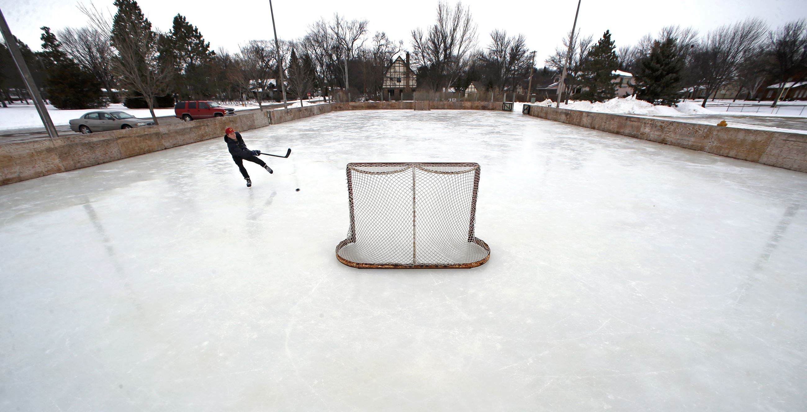 Boy playing hockey on outdoor ice rink
