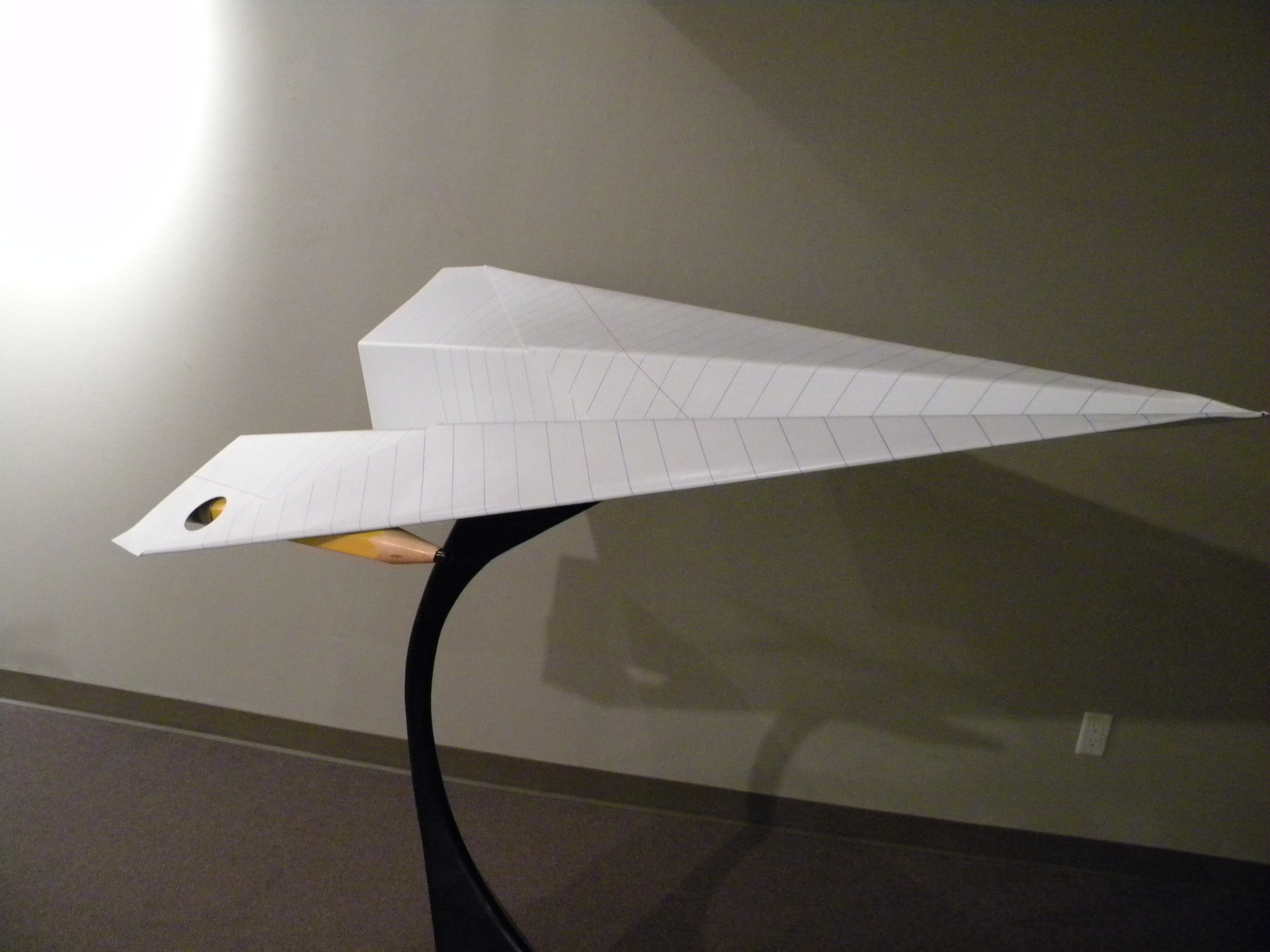 Large steel sculpture that looks like a paper airplane made from a sheet of notebook paper with pencil rockets.