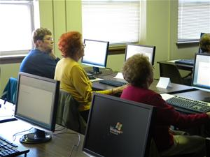 Adults taking a computer class